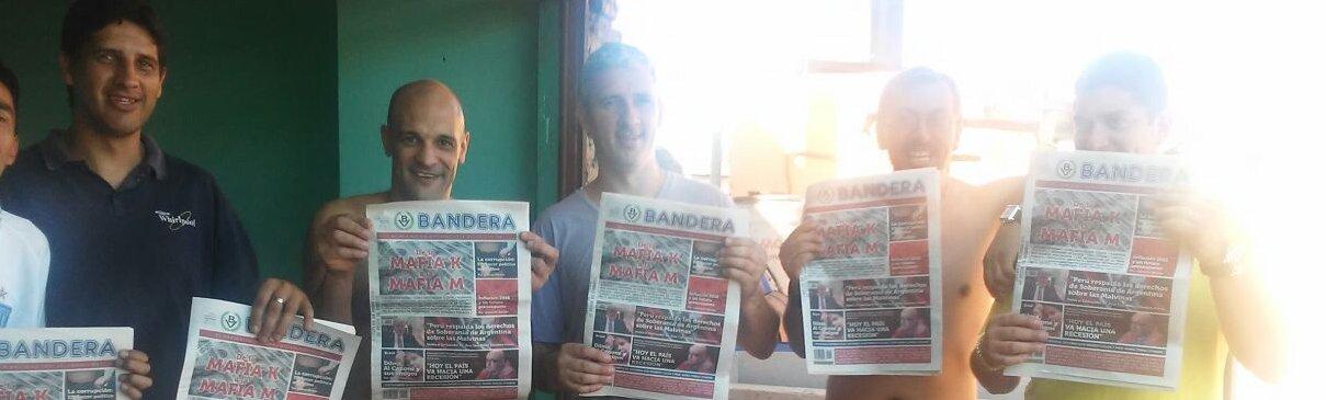 Vecinos de Villa Lugano exhibiendo sonrientes el periódico Bandera